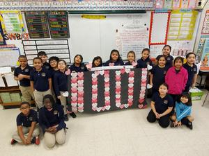 Room 605 student with their banner of 100 reasons
