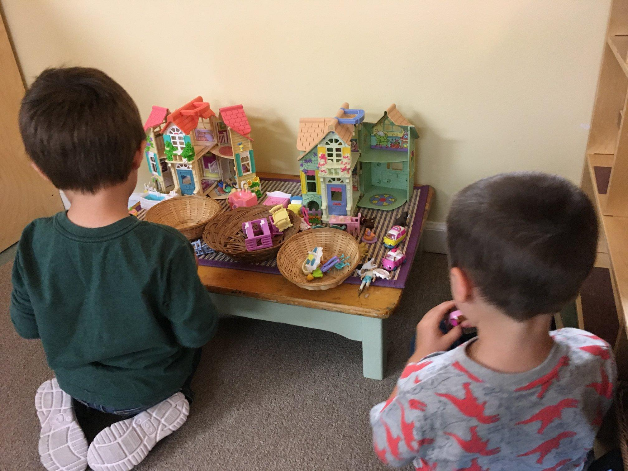 Two children playing with a doll house