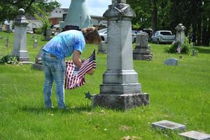 Pic of student replacing flag on grave
