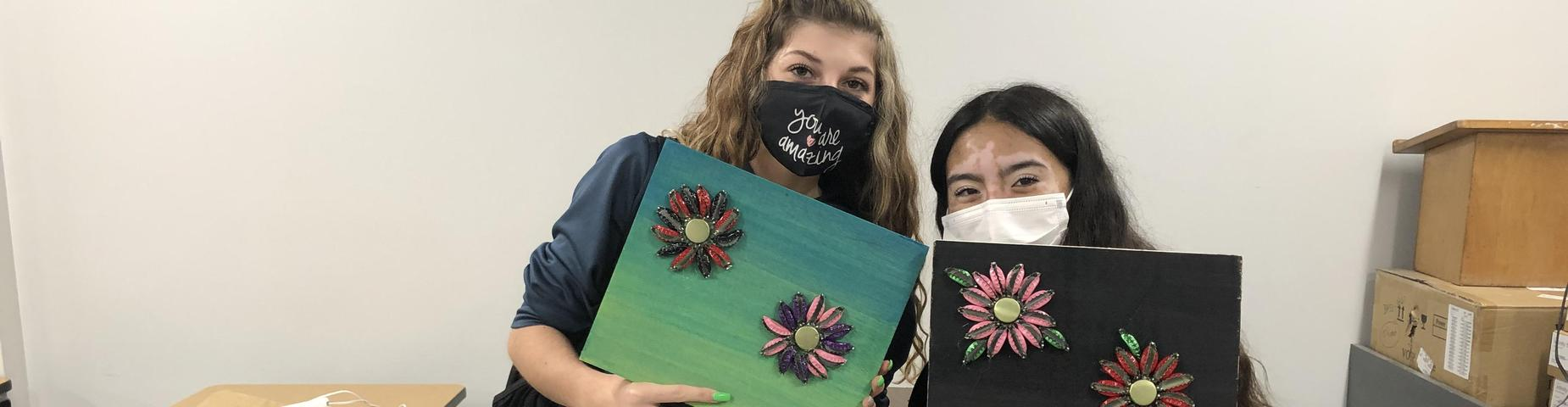 MHS LINKS students showing off their art work using colored bottle caps.