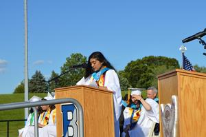Valedictorian, standing at the podium, addresses the class