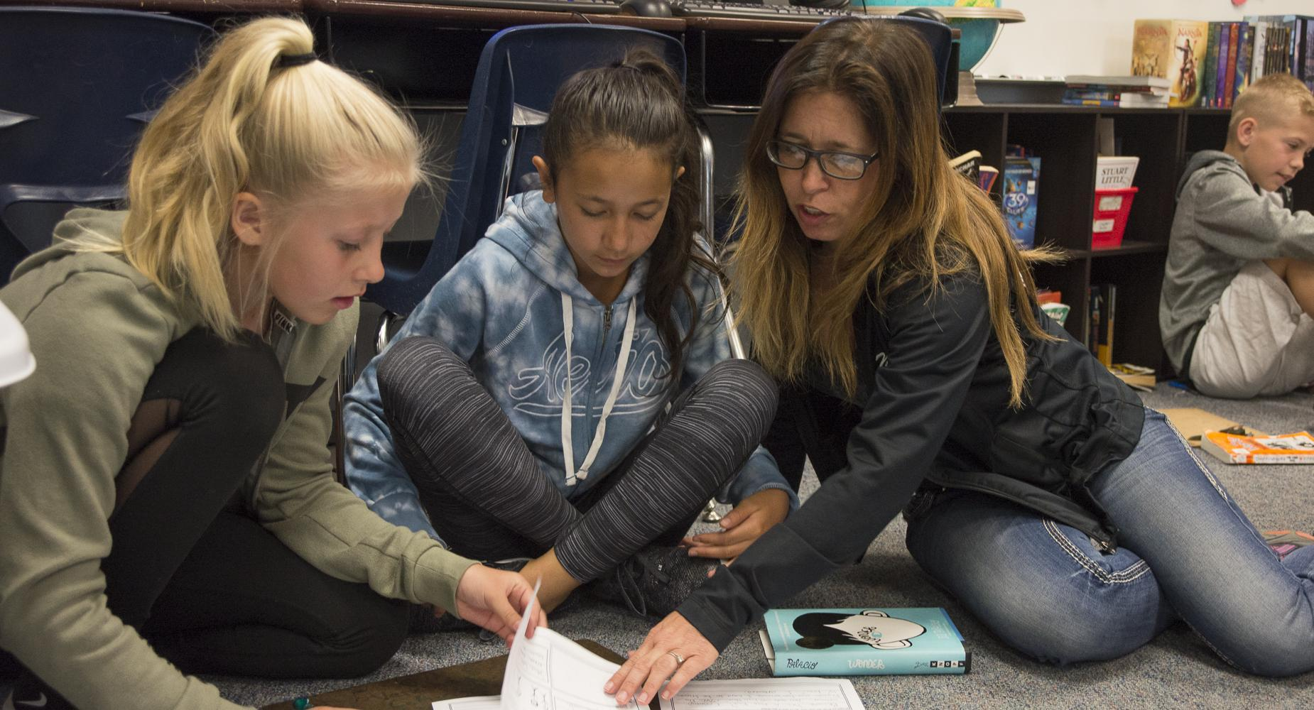 Teacher sits on floor to help two students with workbook