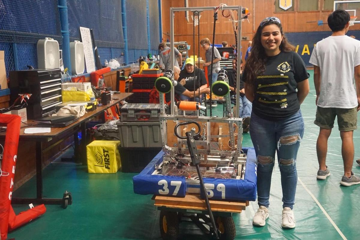 student posing in front of robot