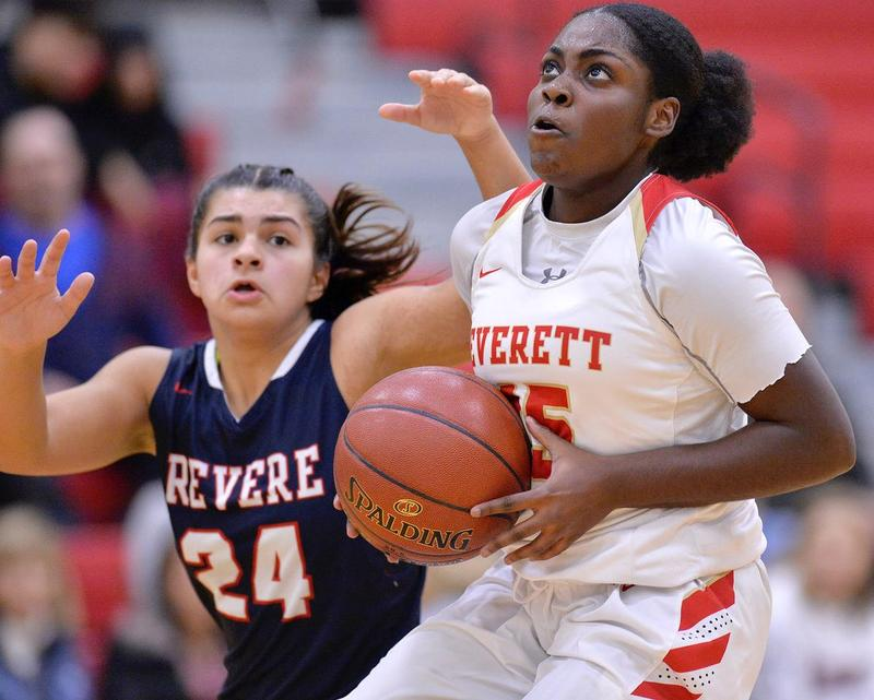 An EHS player clutches the ball as she moves towards the basket
