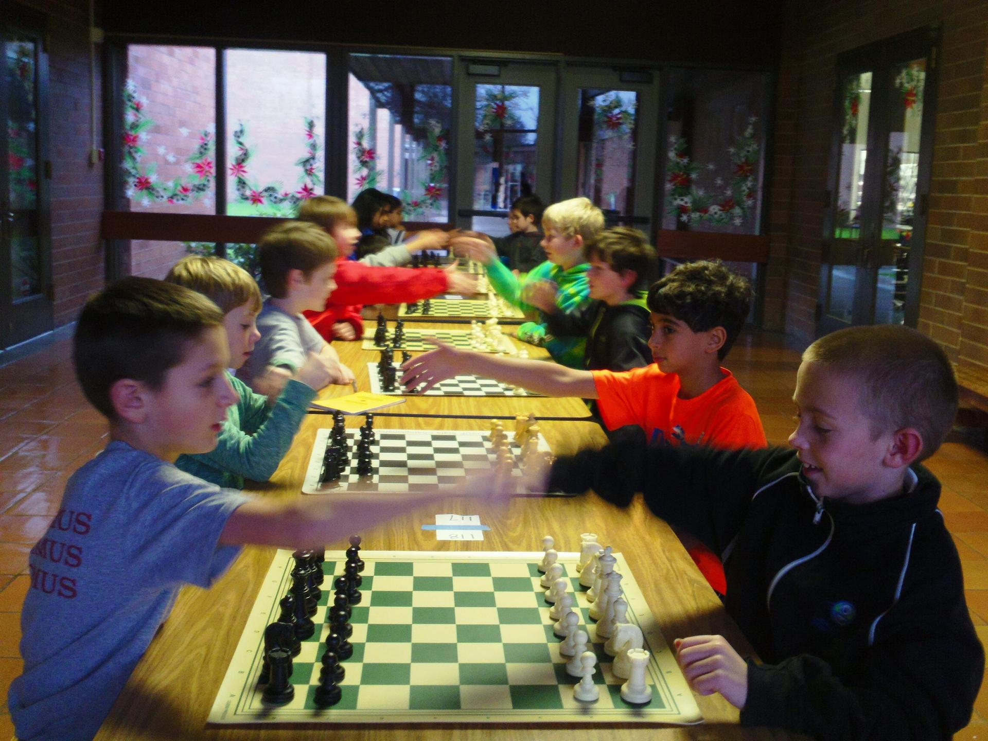 children shaking hands prior to chess matches
