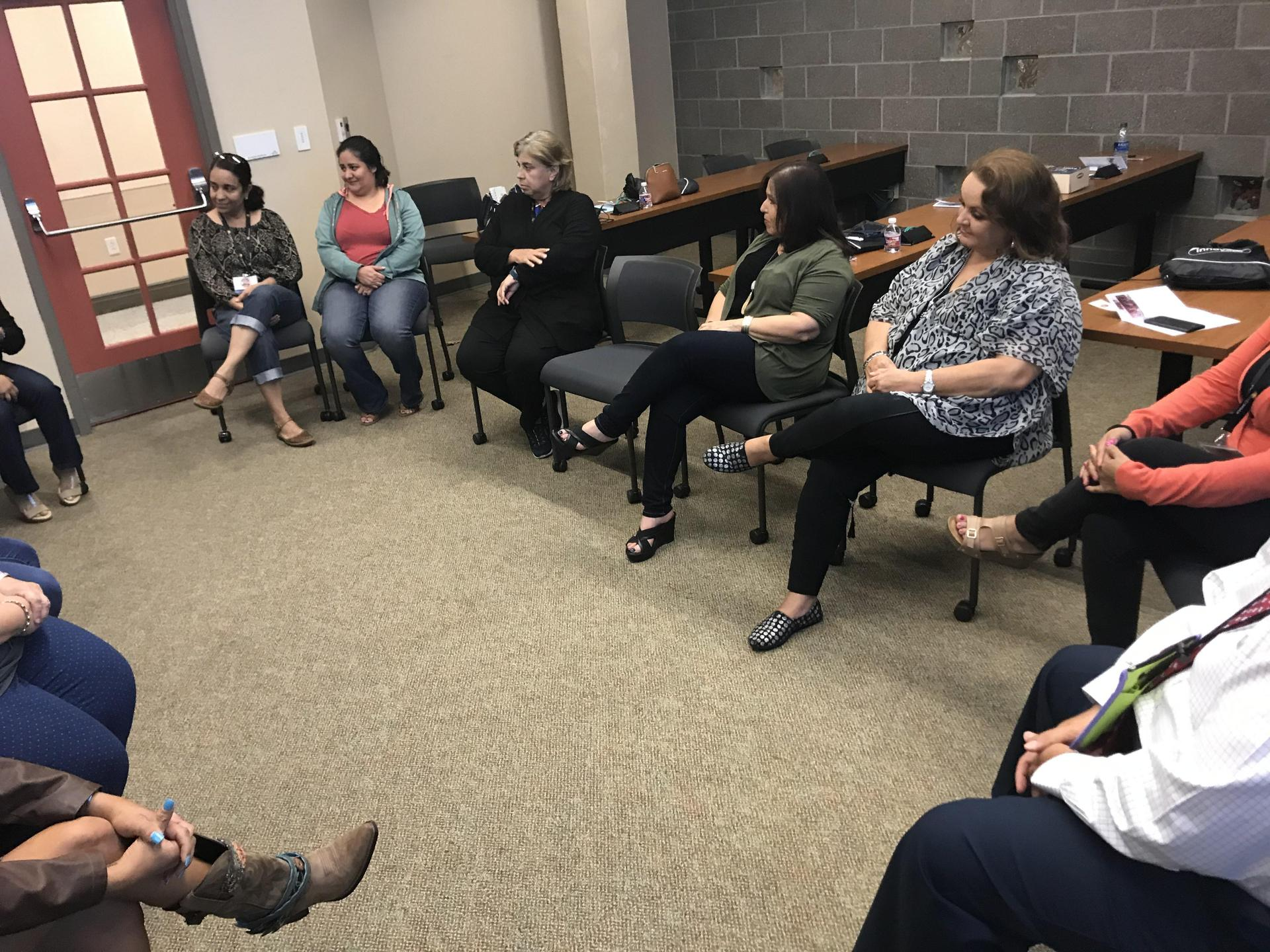Teachers sitting down listening to the presenter