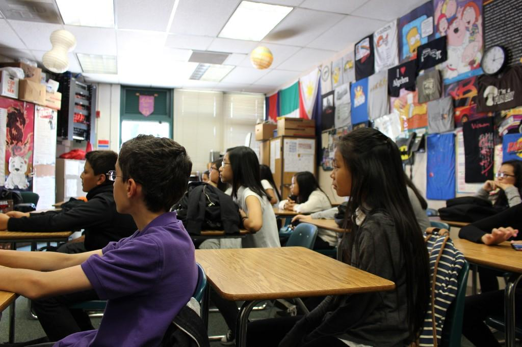 students sit at their desks and listen to a teacher in a classroom