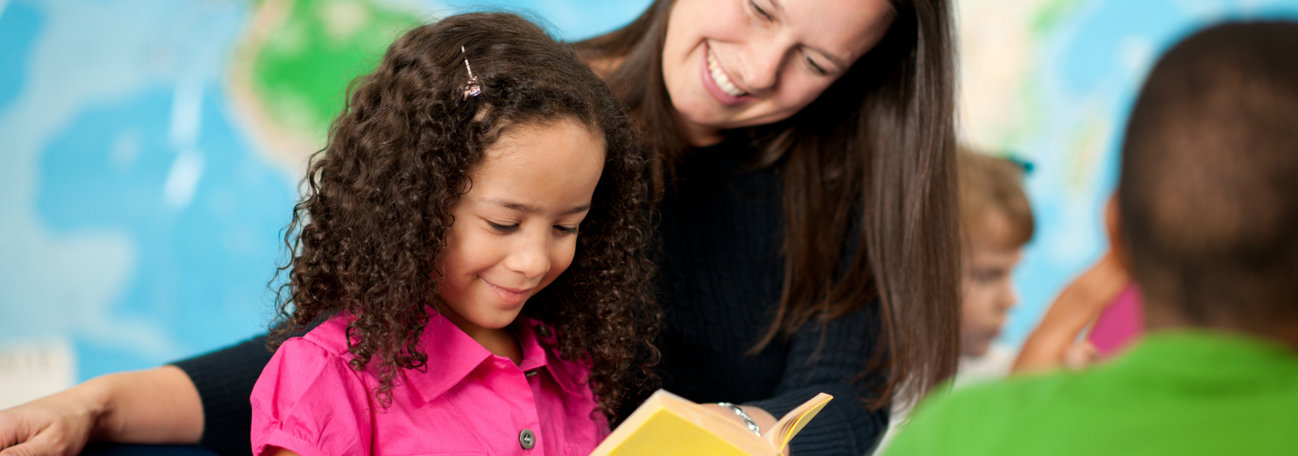 young girl with curly hair looking at a book with her teacher behind her