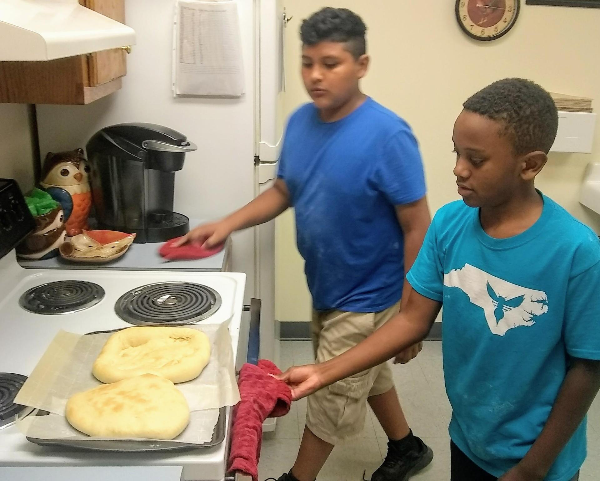 children taking pizza out of the oven