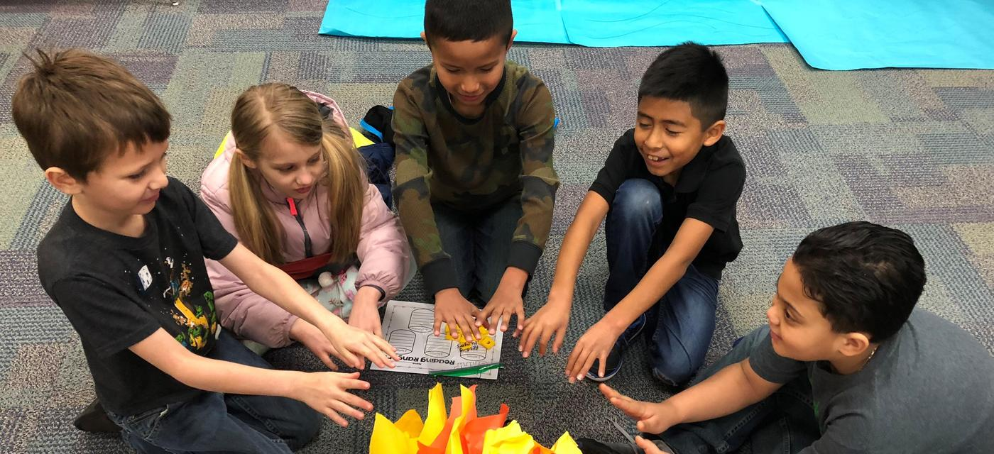 kids pretending to warm their hands around a campfire  made of paper