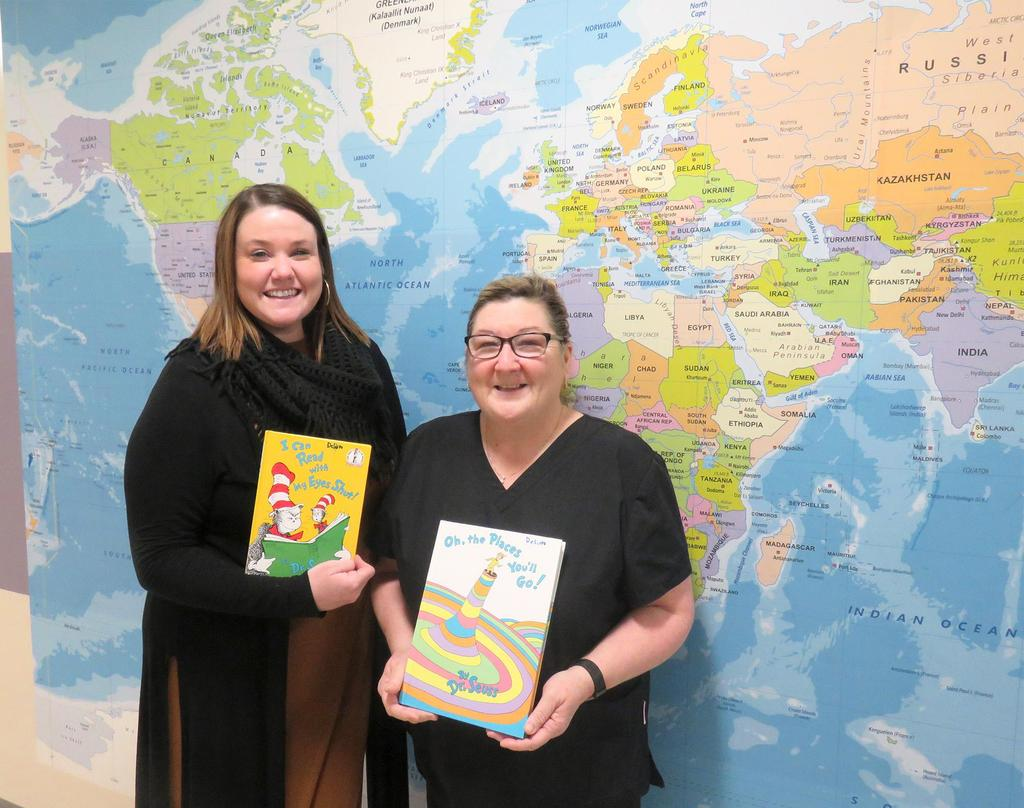 Educator and school nurse, in front of a large map of the world