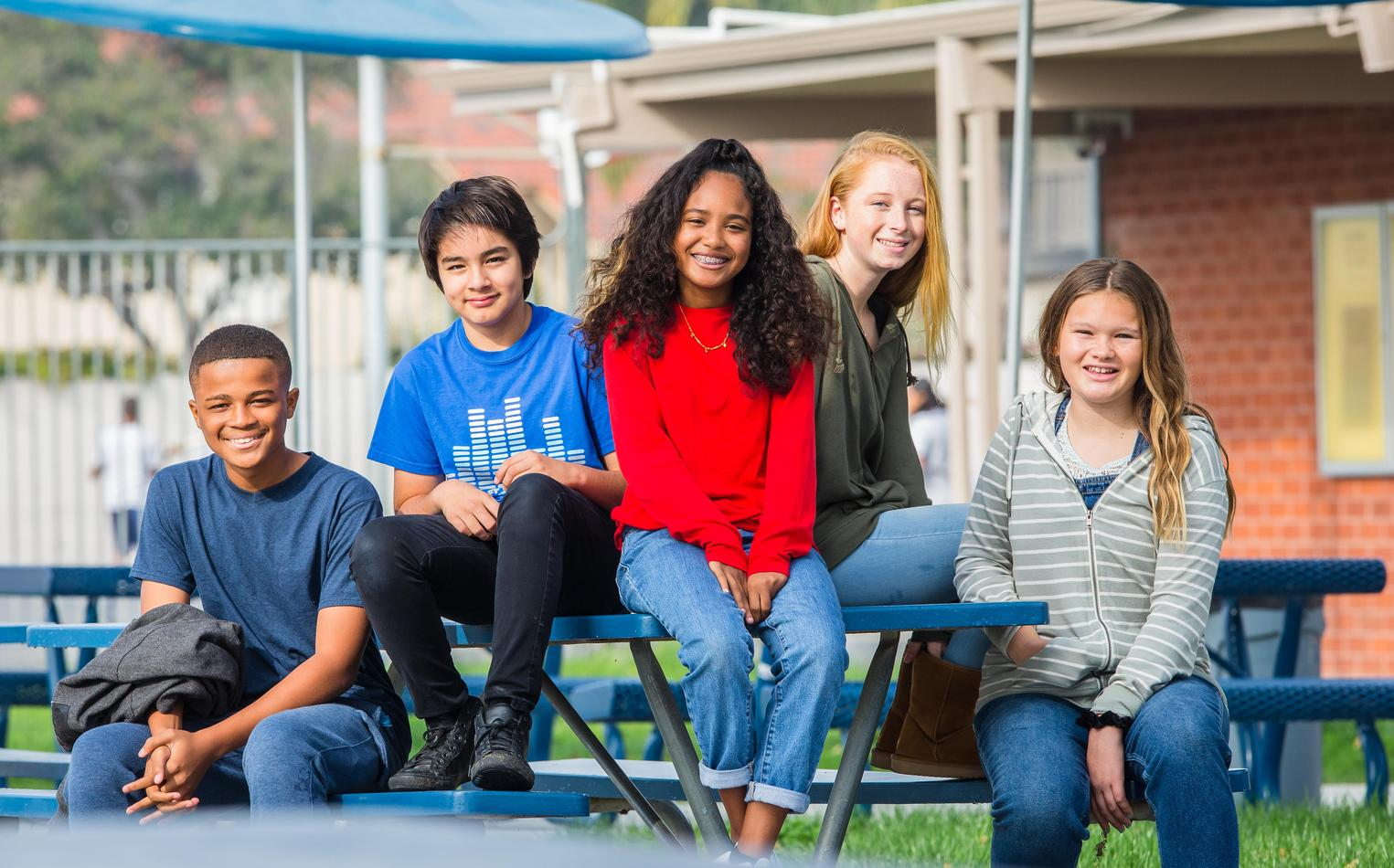 A group of students sitting outside on a lunch bench.