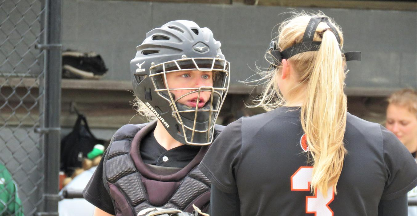 TKHS Softball team catcher and pitcher have a discussion on the mound.