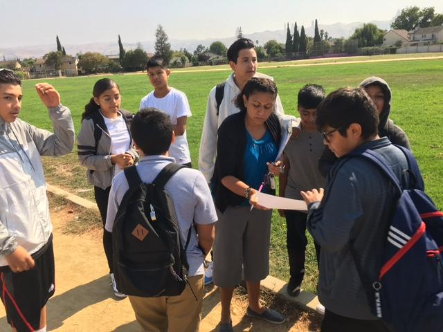 teacher showing students how to reflect eclipse with paper