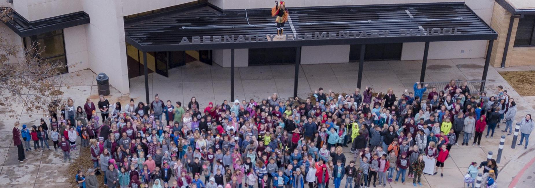 Elementary students pose with principal dressed as turkey atop the building