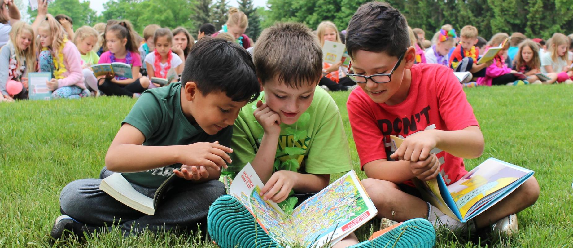 three boys read outside and point at book together on grass
