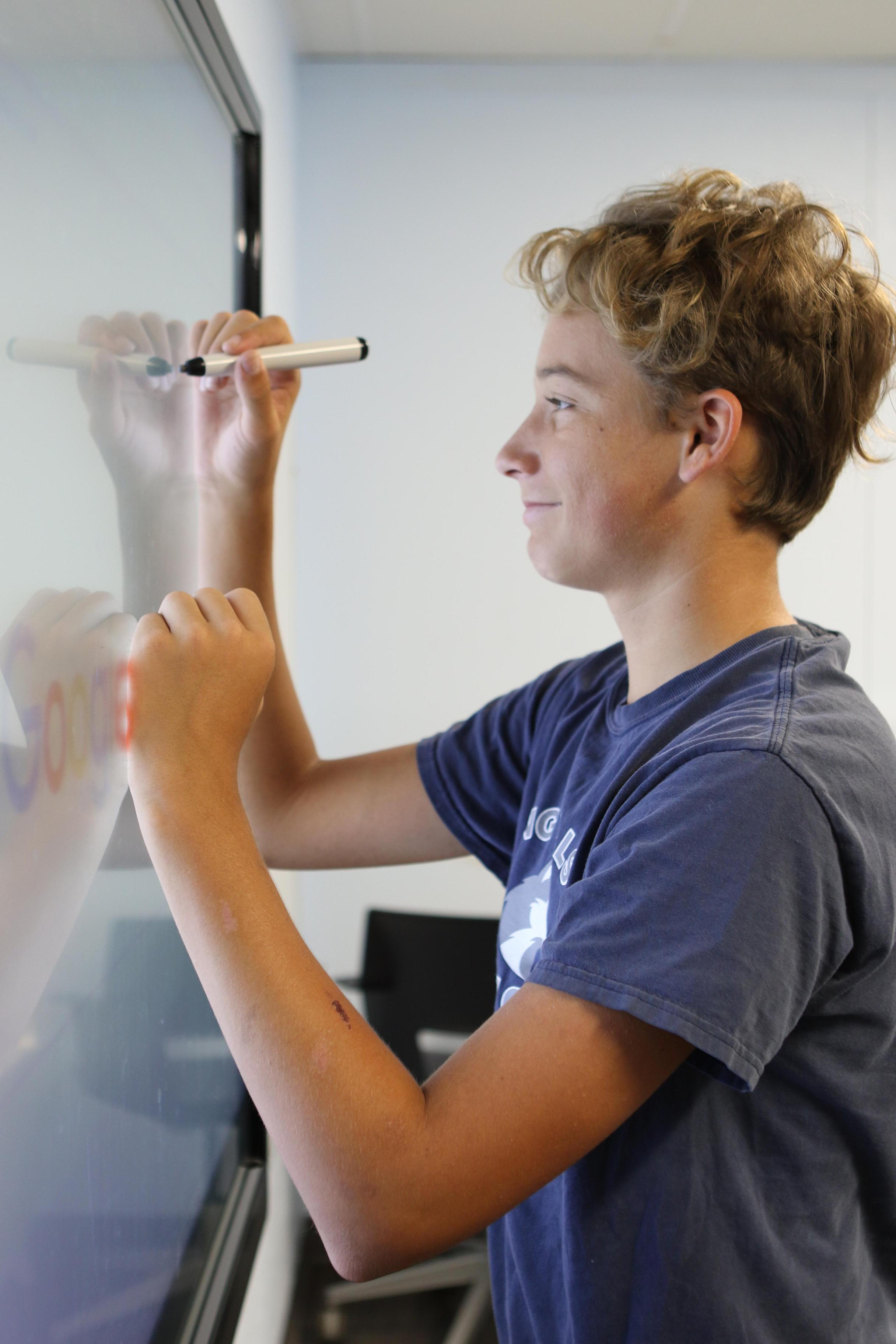 Upper school Renaissance student reviewing work on a digital whiteboard.