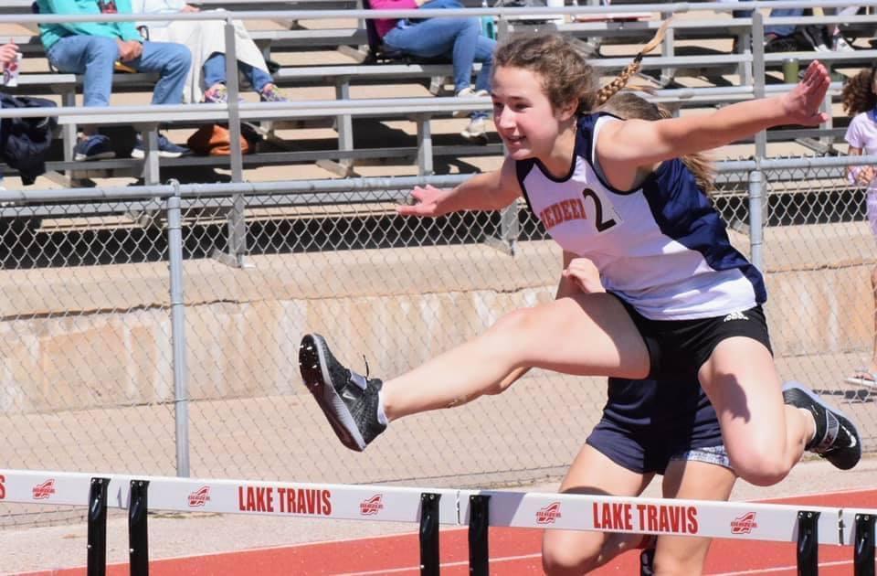 Middle School girl running hurdles