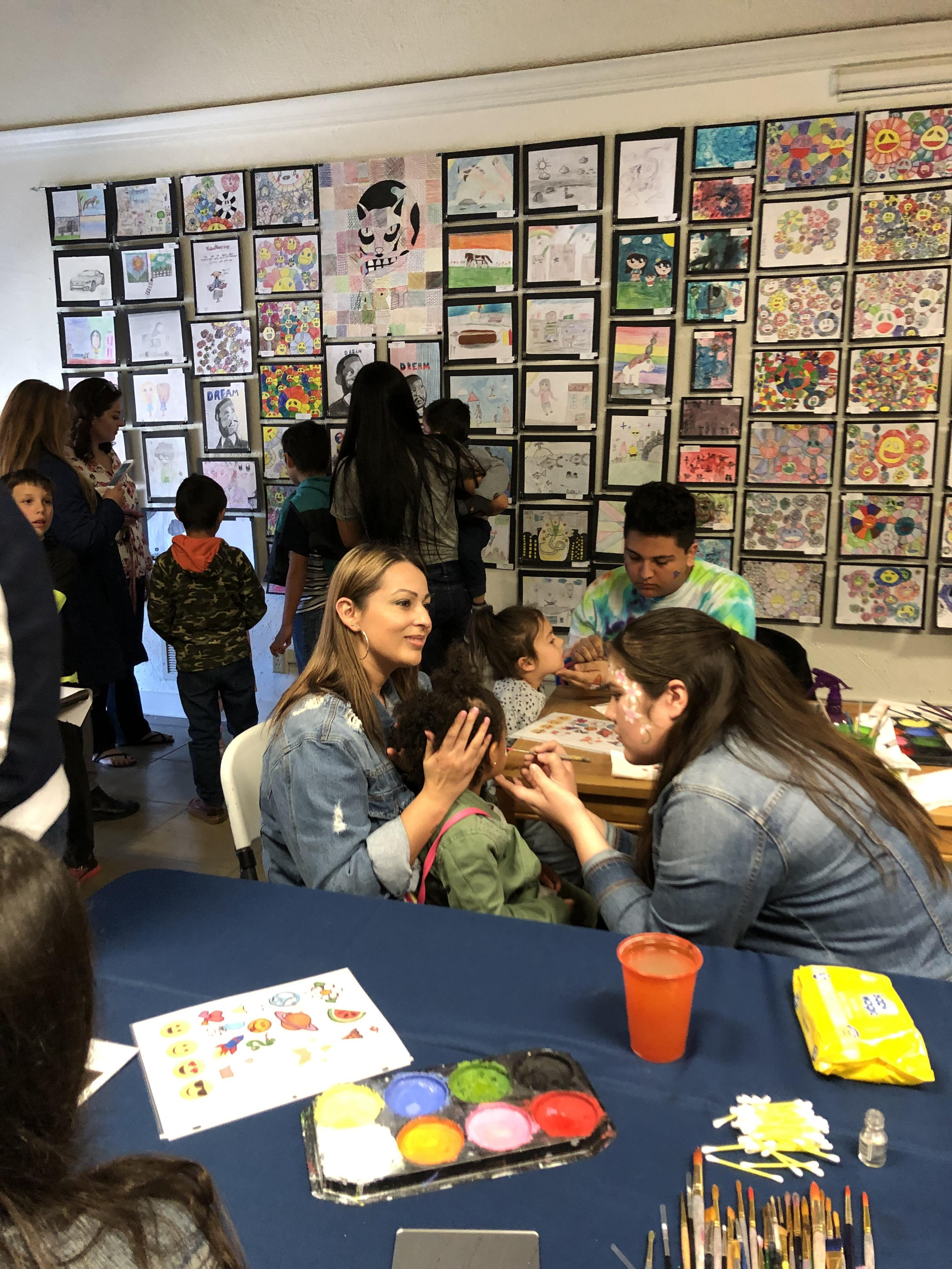 Student having her face painted at the art show