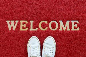red welcome mat with WELCOME in white letters.