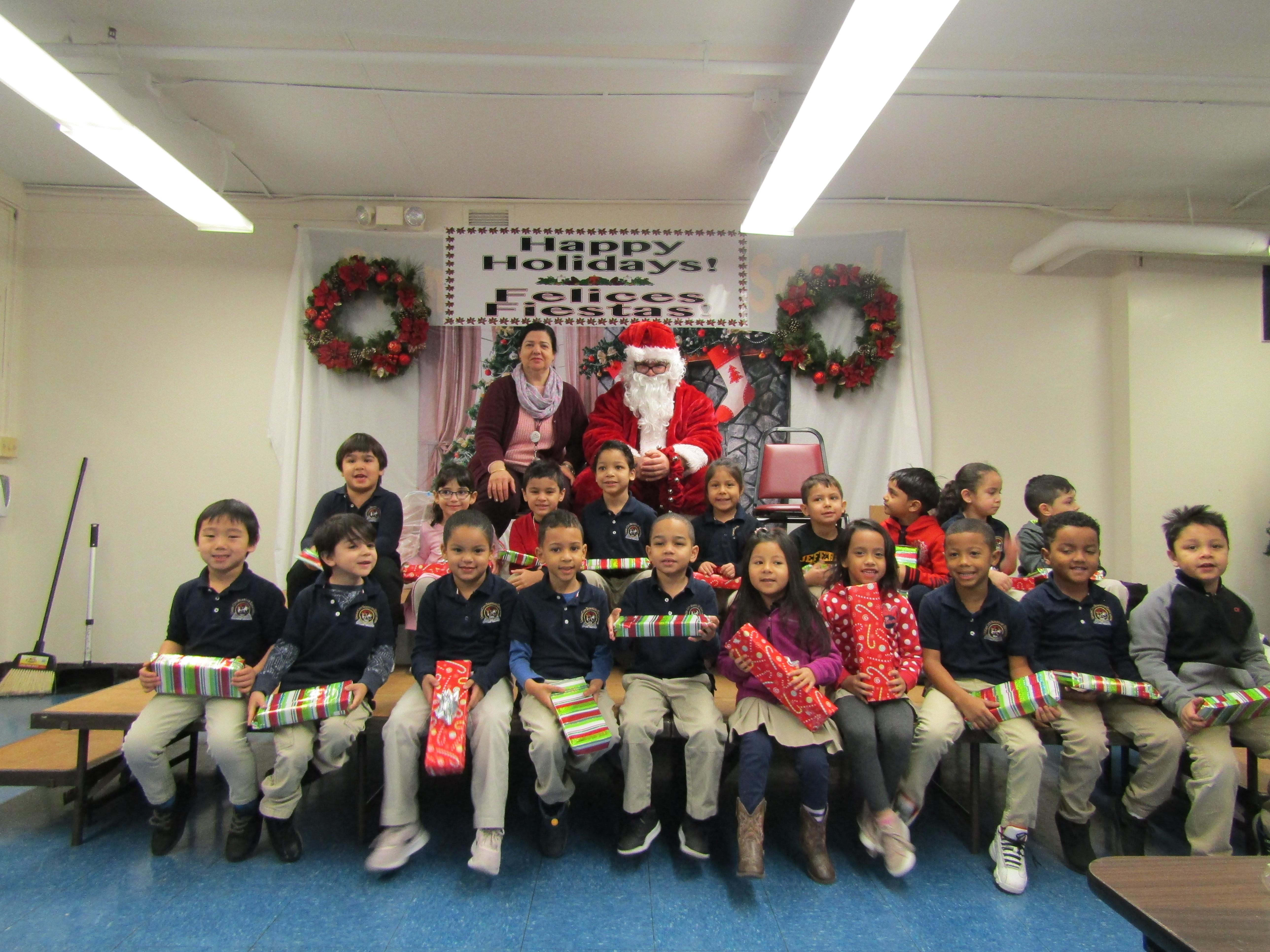 room 101 students holding their gifts with their teacher and santa