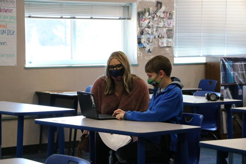 Student working with a teacher in school