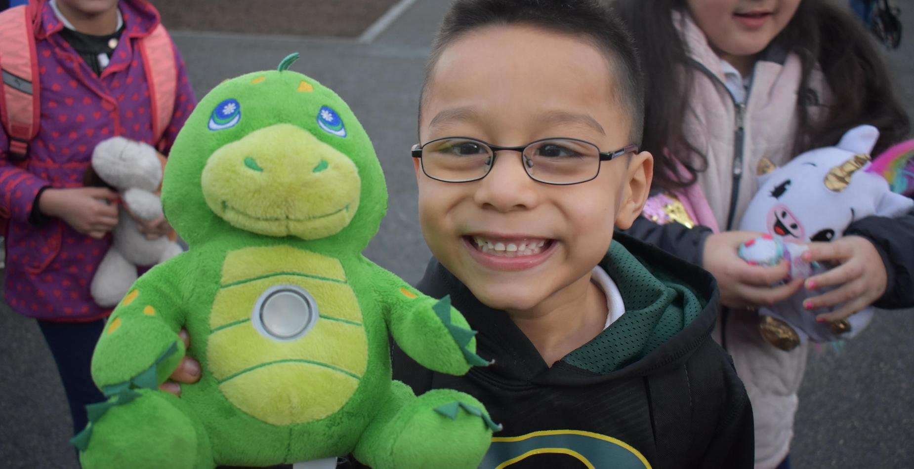 A little boy smiling as he holds his green stuffed animal!