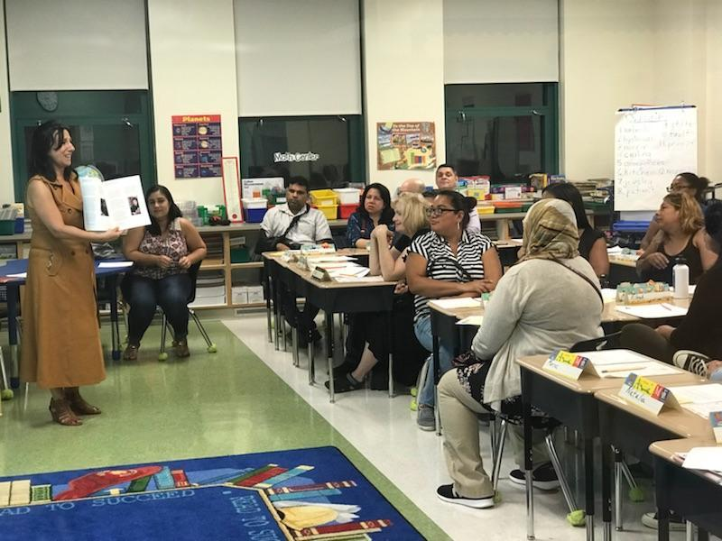 teacher presents to parents the new books that will be used in class