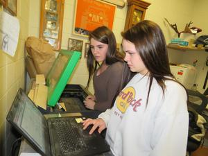Samantha Stayton and Barbar Gillhespy use the laser cutter at school to cut out the ornament pieces.