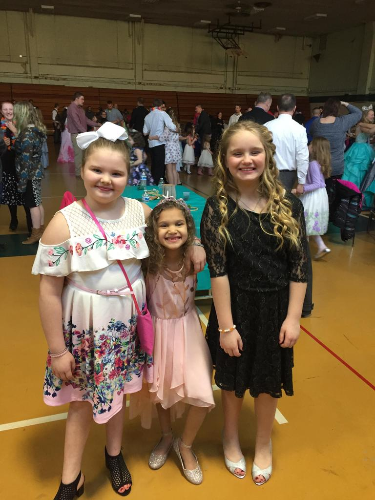 Students smiling for the camera at the Daddy-Daughter Dance