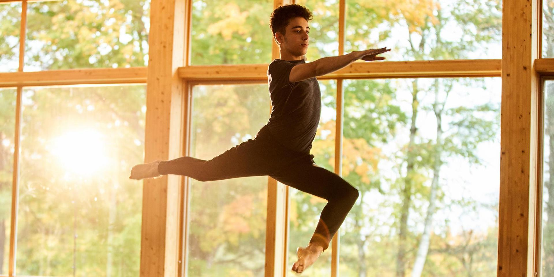 A student practices a leap during a dance class.