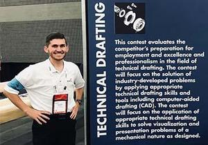 Ben Campbell stands in front of a Technical Drafting banner at the SkillsUSA competition.