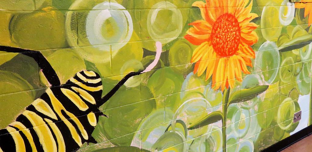 A decorative wall inside the Webster School featuring flowers and a caterpillar