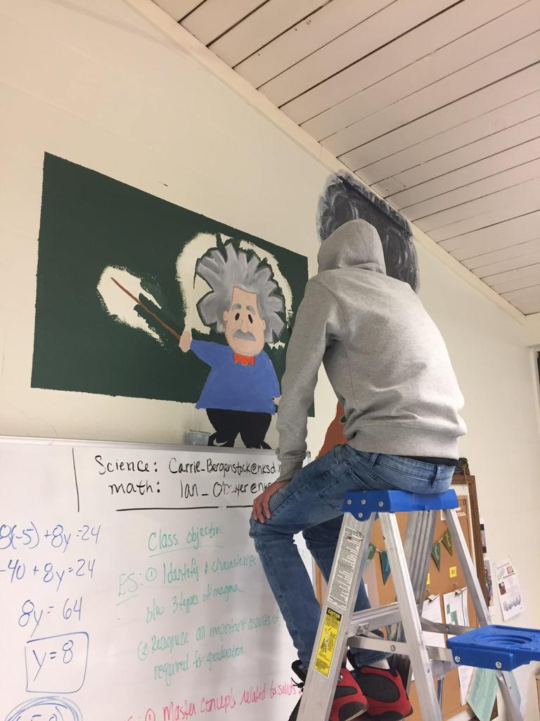 student working on classroom wall mural
