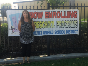Gloria Patton standing in front of a preschool banner.