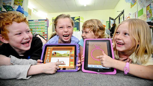 smiling kids working on iPad