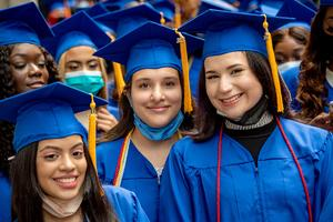 A group of young girsl in blue graduation robes with blue graduation hats and gold tassels