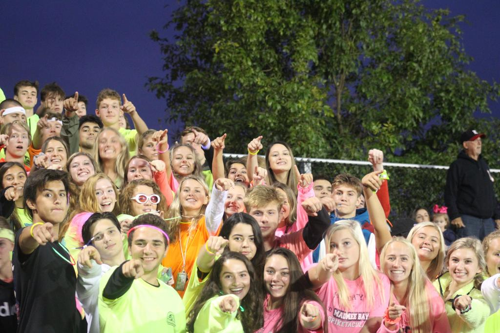 Students standing in the bleachers wearing neon t-shirts