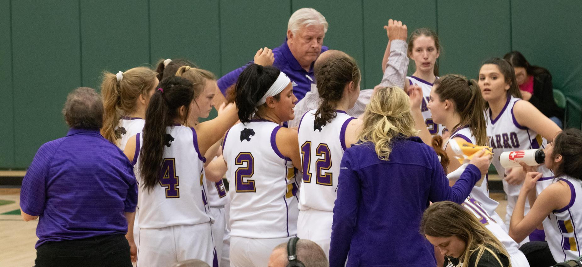Girls huddled during basketball game