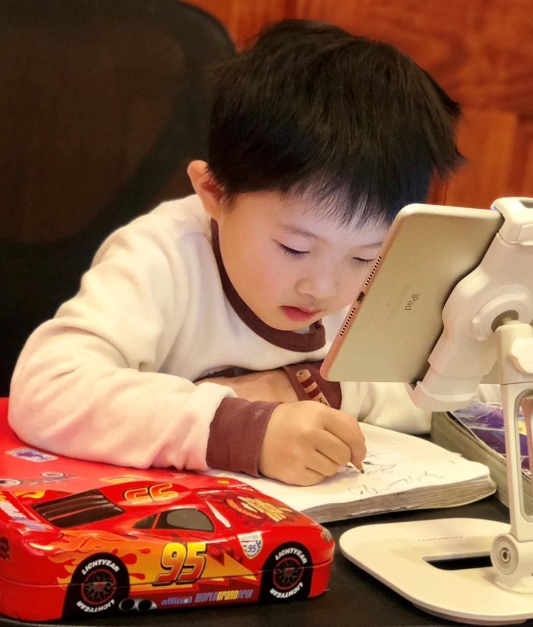Student at home during remote learning. He is at his desk with his ipad and is writing in a notebook.