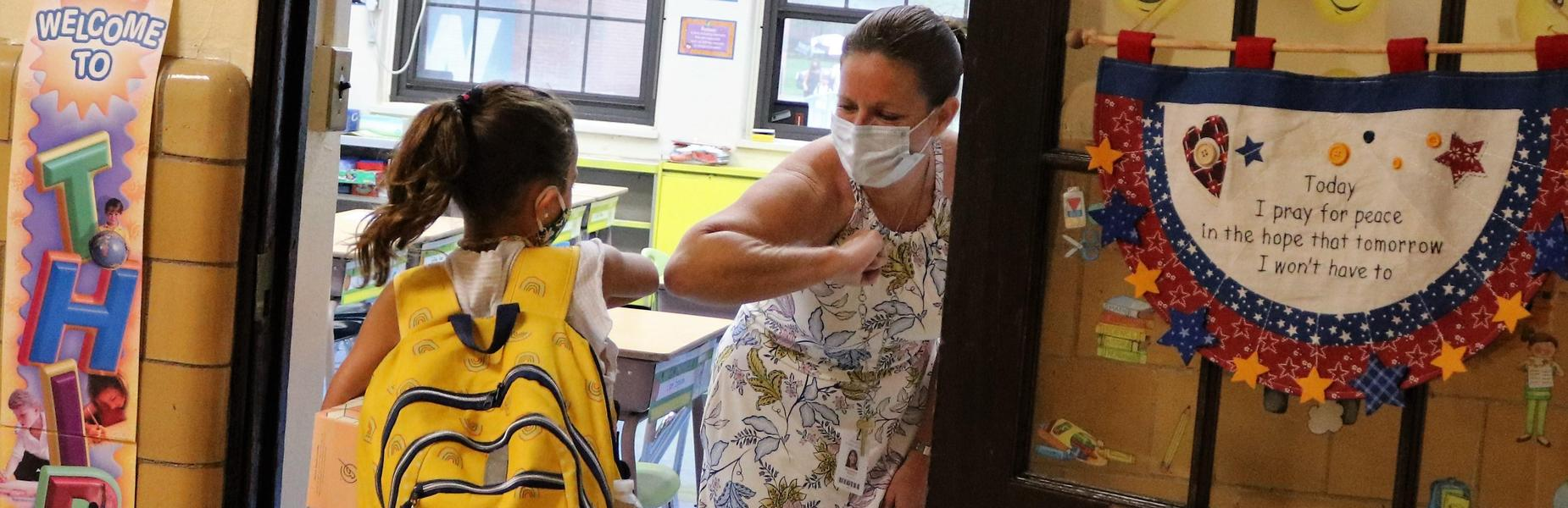 Wilson School third grade teacher Maureen Willis exchanges elbow bumps with her students as they arrive for their first day of school on Sept. 10.