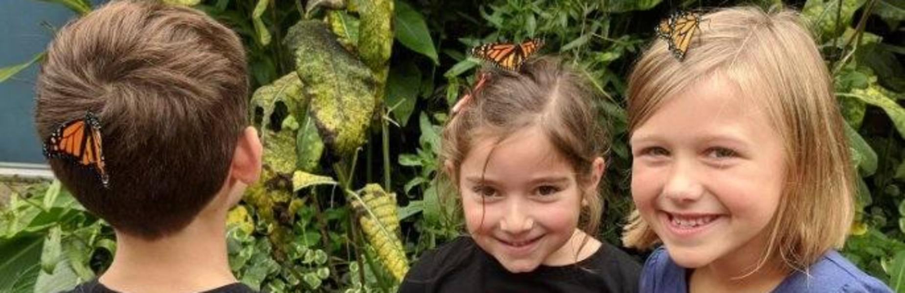 Three 1st grade students at Tamaques smile widely as Monarch butterflies perch on their heads in the school's Monarch Butterfly Way Station.