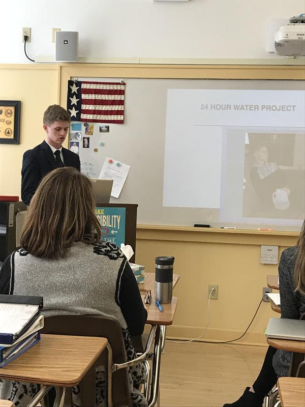 A photo of a student standing at a podium in a classroom making a speech