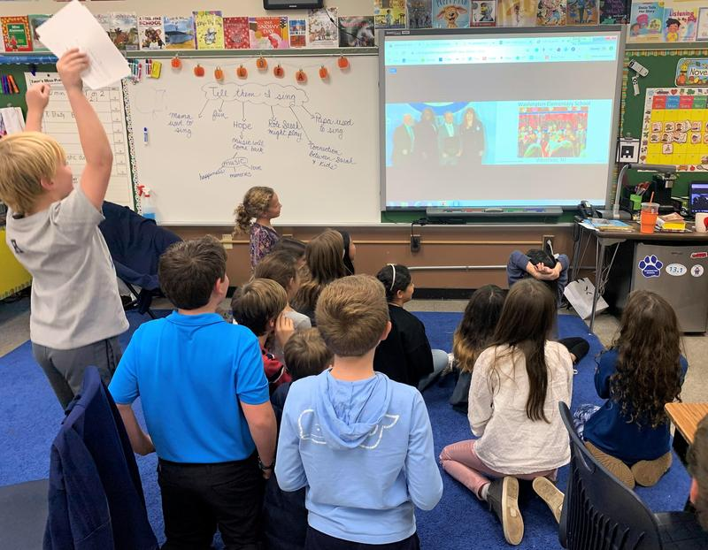 Photo of Washington students cheering and watching livestreamed National Blue Ribbon Schools ceremony as Washington school principal, teacher and district superintendent accept award on behalf of school community.