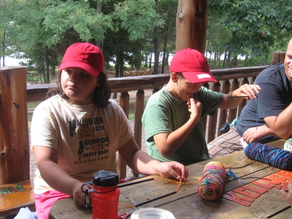 students create yarn craft on cabin porch
