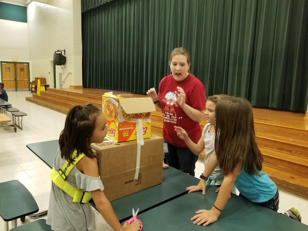 Teacher trying out a cardboard arcade game.