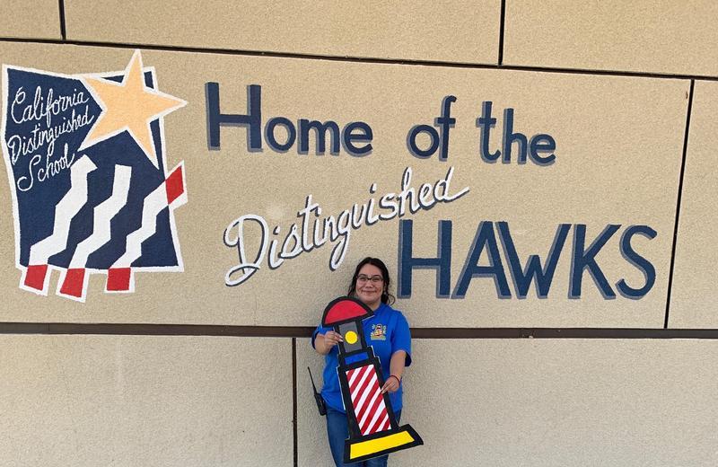 Marlene Saucedo holding a SAFE logo sign.