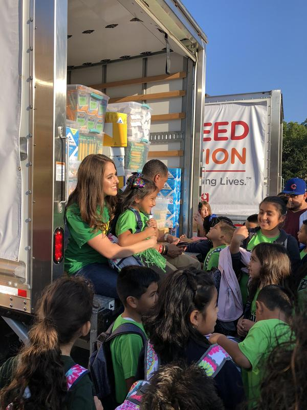 Ms. Bermudez and students seated on the supply truck.