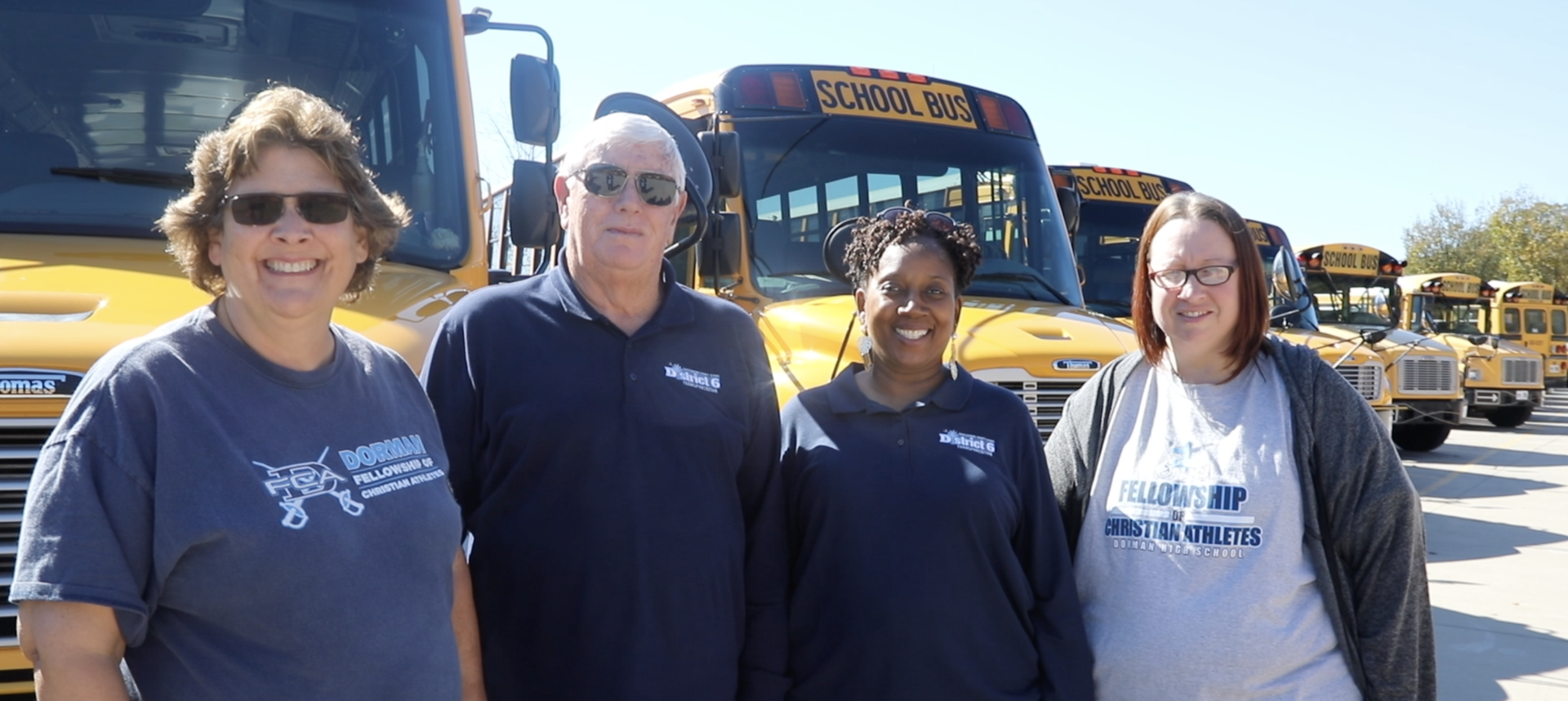 A picture of four drivers standing in front of the bus.