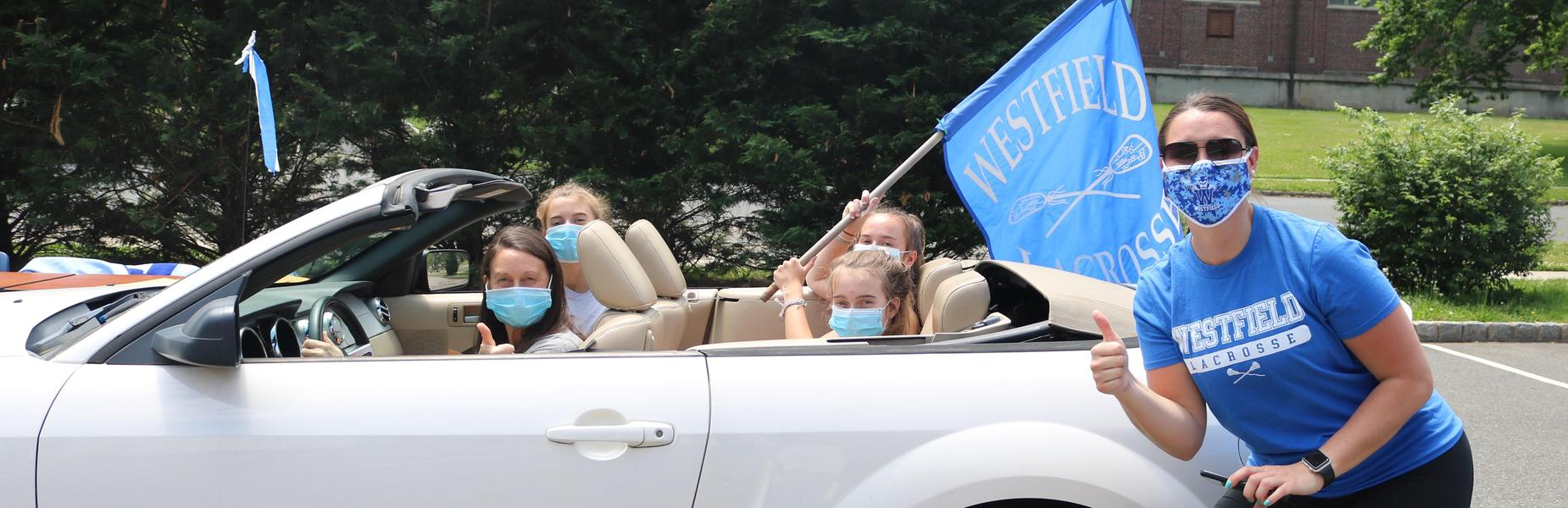 Photo of coach next to players in car as they drive thru to pick up varsity letters during COVID-19 restrictions.